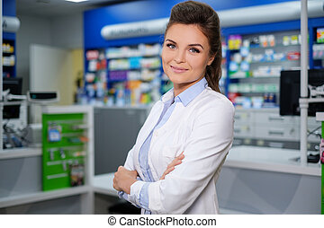 Portrait of beautiful smiling young woman pharmacist standing in pharmacy.
