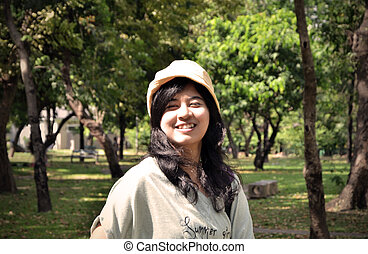 Portrait of beautiful smiling young woman in yellow hat, against background of summer green park, Sepia toned