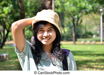 Portrait of beautiful smiling young woman in yellow hat, against background of summer green park