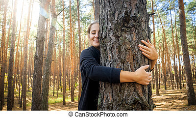 Portrait of beautiful smiling young woman leaning and hugging big old tree in forest. Concept of love, ecology protection and harmony with nature