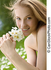 portrait of beautiful teen girl with white flowers in the park
