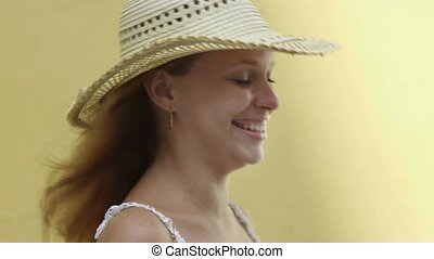 young adult blonde woman in straw hat laughing against yellow wall