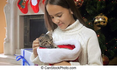 Portrait of beautiful teenage girl caressing cute kitten sitting in Santa cap next to Christmas tree
