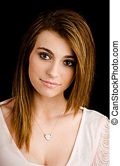 Portrait of beautiful teenage girl with serious expression isolated on black