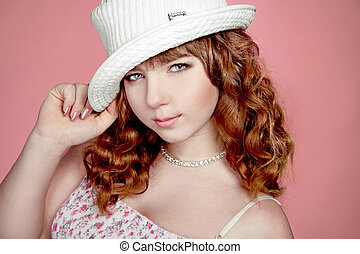 Portrait of beautiful teenager girl with red curly hairs and hat