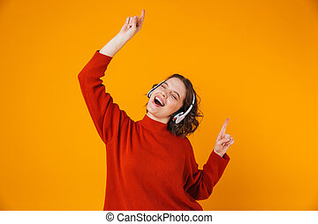 Portrait of beautiful woman 20s wearing wireless headphones dancing and singing while standing isolated over yellow background