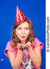 Portrait of beautiful woman blowing confetti in the air, party new years eve celebration on blue background
