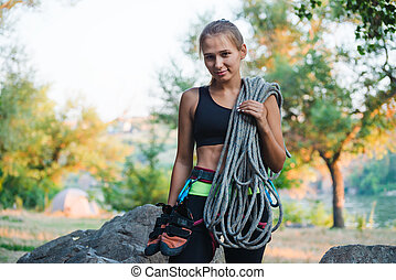 Portrait of Beautiful Woman Climber Holding the Rope near the Rock. Adventure and Extreme Sport Concept
