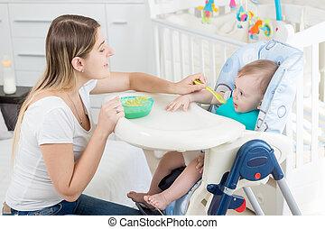 Portrait of beautiful woman feeding 9 months old baby boy...