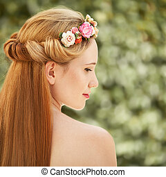Portrait of beautiful woman. Flowers hairstyle.