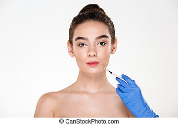 Portrait of beautiful woman getting injection in her lips with botox having plastic surgery in clinic over white background