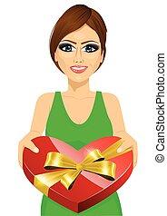 woman handing over a heart shaped box