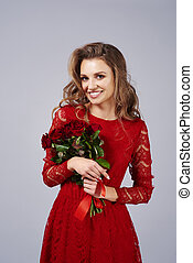 Portrait of beautiful woman holding a bunch of red roses