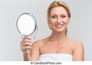 Portrait of beautiful woman holding mirror. smiling woman looking at camera on white