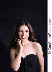 Portrait of beautiful woman in black dress with curly hair - isolated on black background.