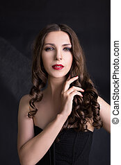 Portrait of beautiful woman in black dress with curly hair - isolated on dark background.