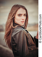 Portrait of beautiful woman in leather coat outdoors