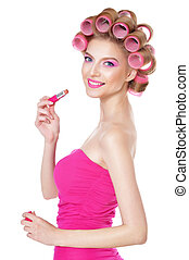 woman in pink dress with hair curlers