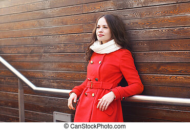 Portrait of beautiful woman in red jacket on against a wooden wall