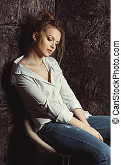 Portrait of beautiful woman in shirt sitting on a chair