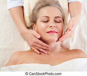 portrait of beautiful woman in spa environment. middle aged woman doing facial massage in a spa salon