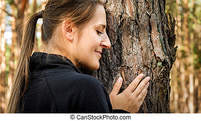 Portrait of beautiful woman leaning and touching old tree in forest. Concept of ecology, environment protection and harmony with nature