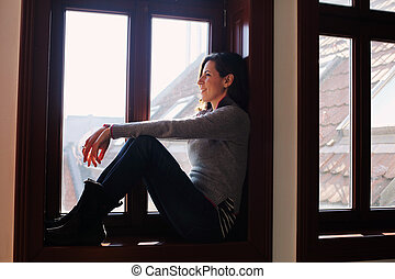 Portrait of beautiful woman looking throught the window