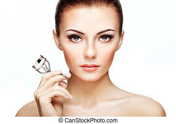 Portrait of beautiful woman making curl eyelashes. Beautiful woman face. Perfect make-up