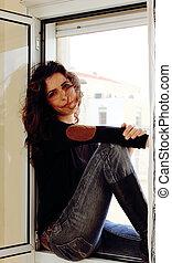 Portrait of beautiful woman near the window