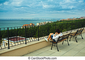 Portrait of beautiful woman on the terrace of prestigious hotel. Sea view
