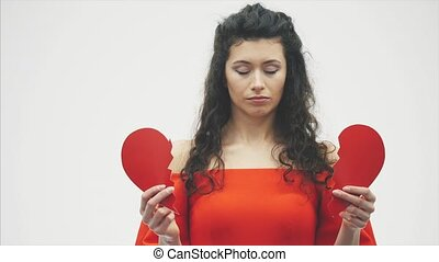 Portrait of beautiful woman on white background. Bad Valentine's Day. Concept, model holds red heart in hand.