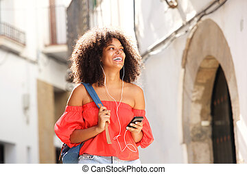 Portrait of beautiful woman outside on street with headphones and smart phone