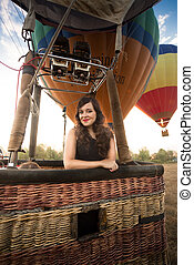Portrait of beautiful woman posing at hot air balloon basket