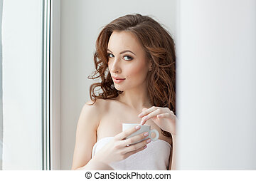 Portrait of beautiful woman posing with cup