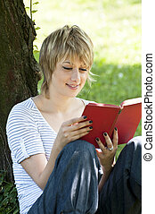 Portrait of beautiful woman reading in nature
