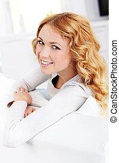 Portrait of beautiful woman sitting in sofa