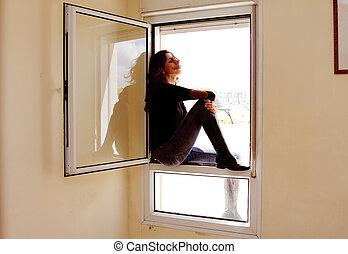 Portrait of beautiful woman sitting on the window