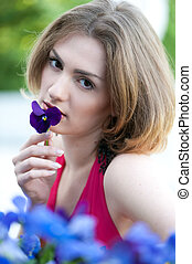Beautiful woman smelling flower.
