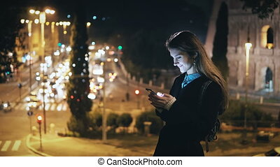 Portrait of beautiful woman standing near the traffic road and Colosseum in Rome, Italy and using the smartphone.