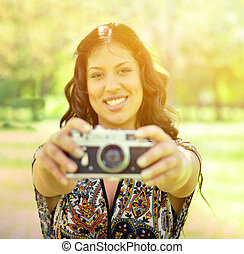 Portrait of beautiful woman taking picture mwith vintage camera