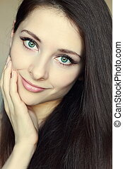 Portrait of beautiful woman touching clean face with green ...