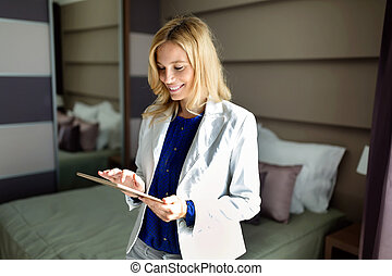 Portrait of beautiful woman using tablet in bedroom