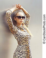 Portrait of beautiful woman wearing a leopard dress and sunglasses posing in the city
