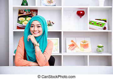 beautiful woman wearing hijab at living room with decorated...