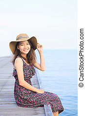 portrait of beautiful woman wearing long dress and straw hat...
