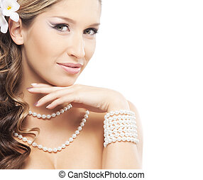 Portrait of beautiful woman with a pearl jewelry and a flower in her hair isolated on white background