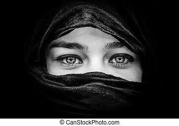 Portrait of beautiful woman with blue eyes wearing black scarf in black and white