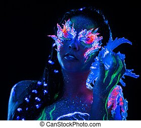 Portrait of beautiful woman with body art glowing in ultraviolet light