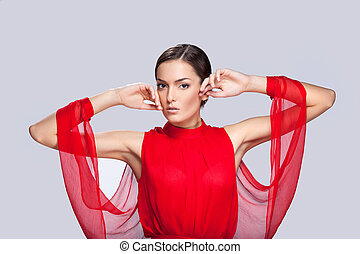 portrait of beautiful woman with clean face skin. Glamorous young woman in red on grey background and raised hands up