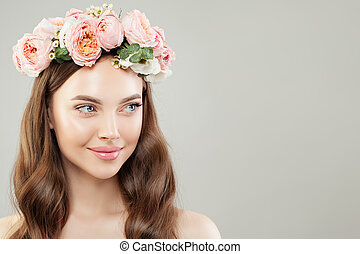 Portrait of beautiful woman with clear skin and flowers on white. Natural beauty